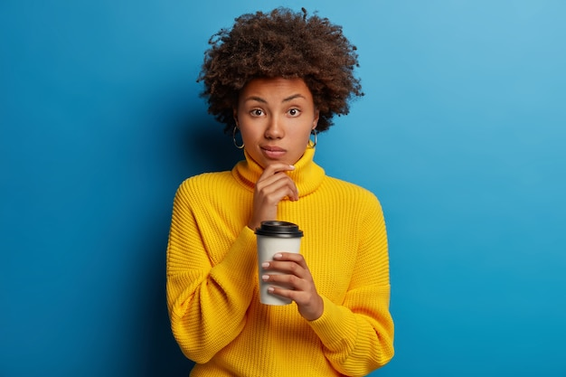 Afro american woman dressed in yellow jumper, drinks takeaway coffee, holds cup from cafe