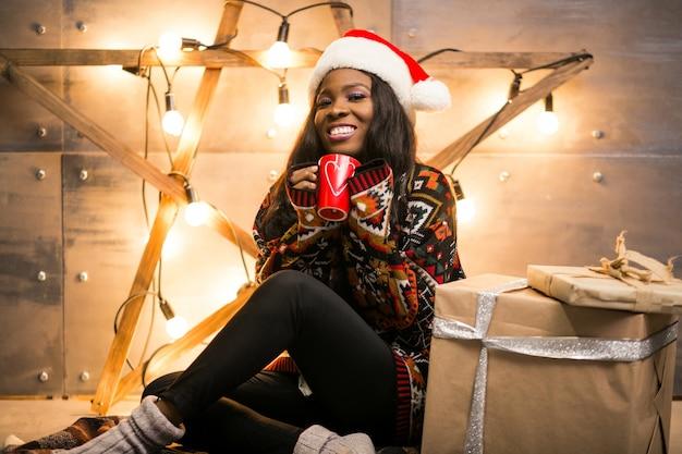 크리스마스 이브에 커피를 마시는 아프리카 미국 여자