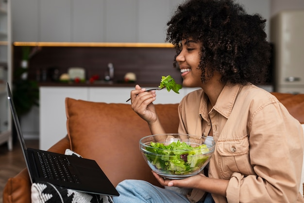 Afro-american woman eating salad and looking on laptop