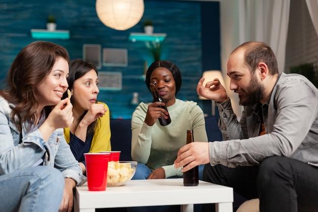 多民族の友達とぶらぶらして楽しんでいるアフリカ系アメリカ人の女性。居間で夜遅くソファに座って一緒に時間を過ごす多民族の人々のグループ。