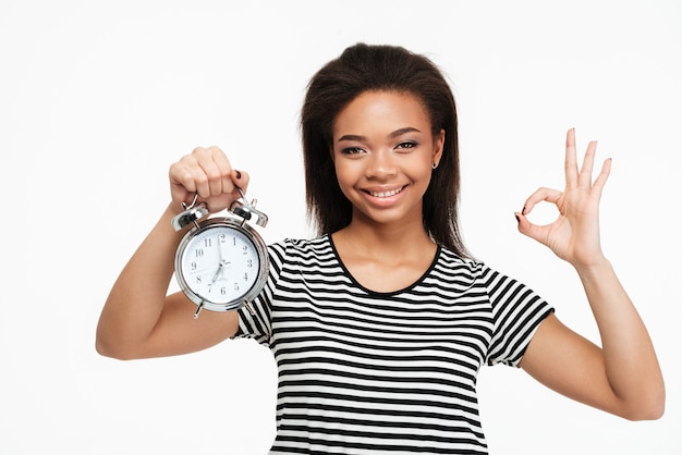 目覚まし時計を押しながらokのしぐさを示すアフロアメリカンの女性