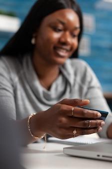 オンラインショッピングをしている経済のクレジットカードを保持しているアフリカ系アメリカ人の女性