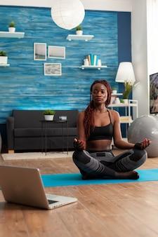 Афро-американская женщина в спортивной одежде сидит и практикует позу лотоса, занимается йогой, сидя на коврике для йоги, одетая в спортивную одежду после онлайн-обучения. тренировки и здоровый образ жизни.