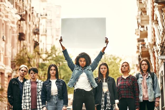 아프리카계 미국인 여성이 길에 서 있는 동안 머리 위에 빈 간판을 들고 있다