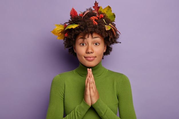 La donna afroamericana tiene insieme i palmi delle mani, prega sincero, ha le foglie autunnali nei capelli, indossa un maglione verde