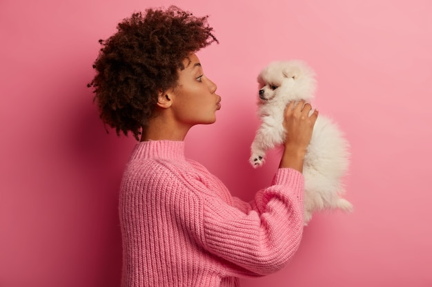 Afro american woman kisses breed dog, raises in hands, wears knitted sweater, poses against pink background