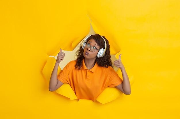 黄色い紙の壁の穴から音楽を聴いているアフリカ系アメリカ人の女性