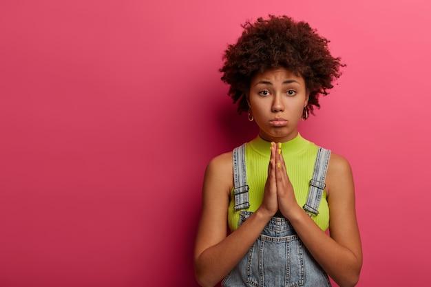 アフロアメリカ人女性は懇願するような顔をし、祈りのジェスチャーで手のひらを保ちます