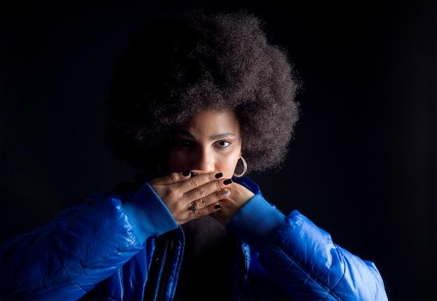 검은 배경에 아프리카 미국 여자는 그녀의 손으로 그녀의 입을 커버