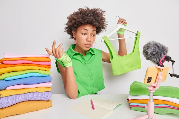 Afro american woman sells clothes online by live streaming holds top on hanger shots clothing review video poses at table with folded laundry focused at smartphone camera