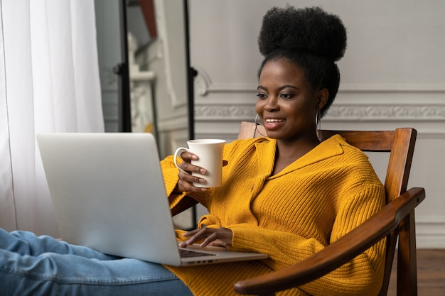 Afro-american woman sitting on chair, watching webinar, working online on laptop, talking in video chat, drinking tea or coffee.