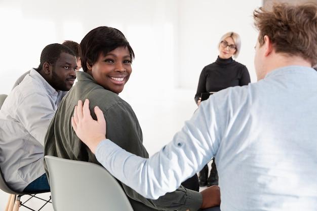 アフロアメリカンの女性の笑顔とカメラマンを見て