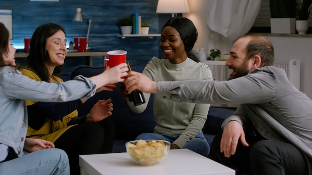 Afro american woman socialising with friends while having fun late at night in living room during ho...