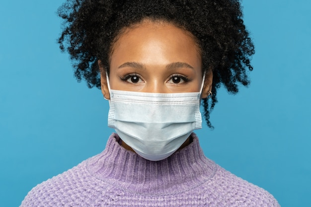 Afro american woman wear face mask during covid coronavirus outbreak or flu season isolated on blue