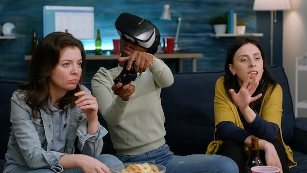 ジョイスティックの手を握ってビデオゲームの競争をしているゴーグルヘッドセットを身に着けているアフリカ系アメリカ人の女性。夜遅くにソファに座って楽しんでいる多民族の友人