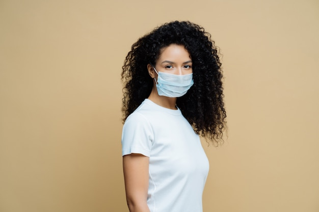 Afro american woman wears protective face mask, protects against spread of coronavirus disease