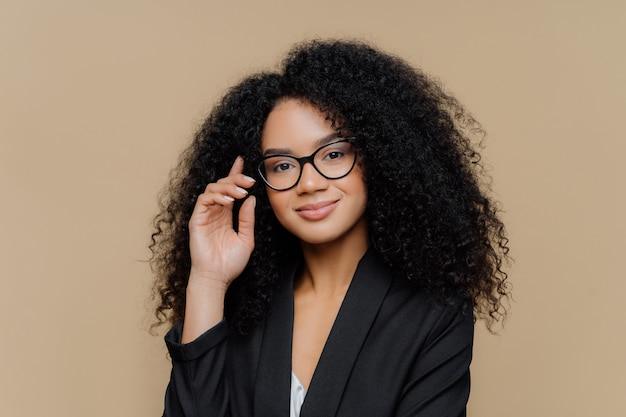 Afro american woman with bushy curly hairstyle, keeps hand raised