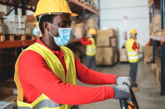 안전 마스크를 착용하는 동안 팔레트 트럭을 당기는 창고 내부 아프리카 미국 노동자