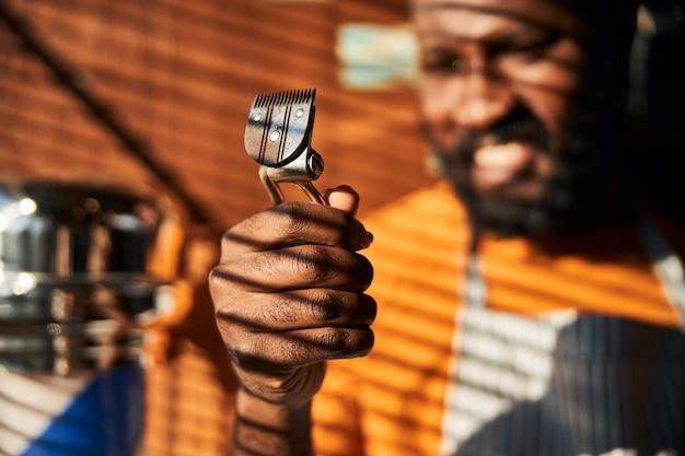 ポータブルバリカンを保持しているアフリカ系アメリカ人の若い男