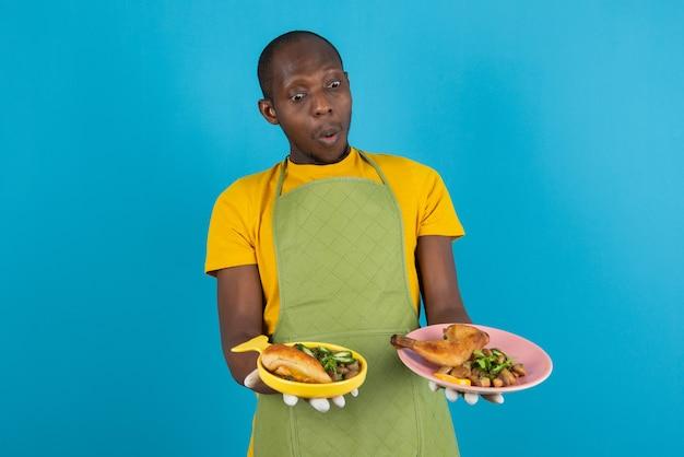 Афро-американский молодой человек в фартуке держит жареную курицу на синей стене