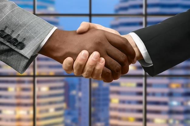 アフロと白人のビジネスマンの握手。高層ビルの前で握手します。自業自得。新しい仲間に会えてうれしい。