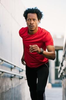 運動をし、屋外で階段を駆け上がるアフロアスレチック男