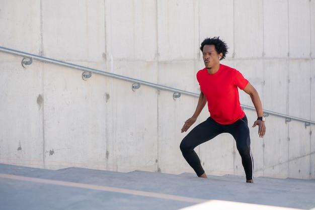 階段で屋外運動をしているアフロアスリート男。スポーツと健康的なライフスタイル。