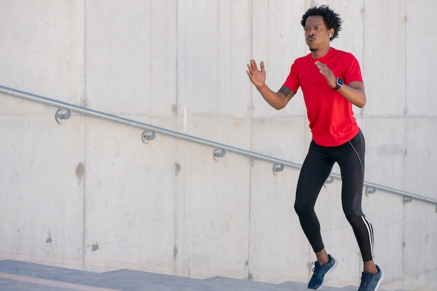 Afro athletic man doing exercise outdoors at stairs. sport and healthy lifestyle.