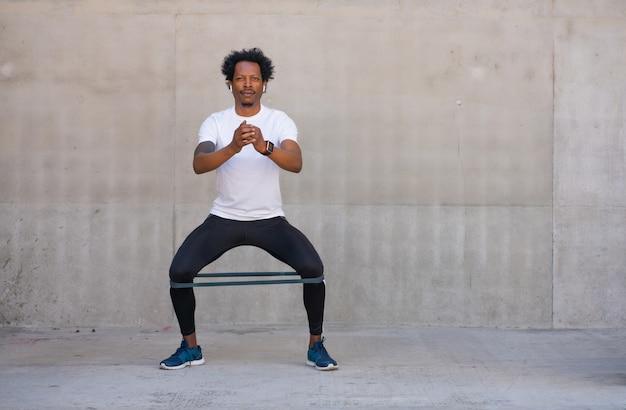 屋外でスクワットレッグを運動してやっているアフロアスリートの男性。スポーツと健康的なライフスタイルのコンセプト。