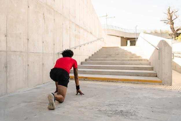 Uomo atletico afro pronto a correre all'aperto sulla strada