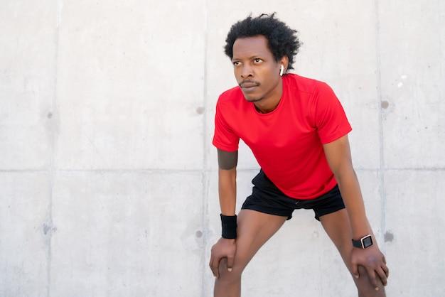 屋外で運動した後に休んでいるアフロアスリートの男性。スポーツと健康的なライフスタイルのコンセプト。