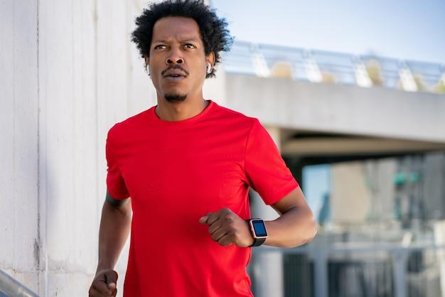 路上で屋外で走ったり運動したりするアフロアスリートの男。スポーツと健康的なライフスタイルのコンセプト。