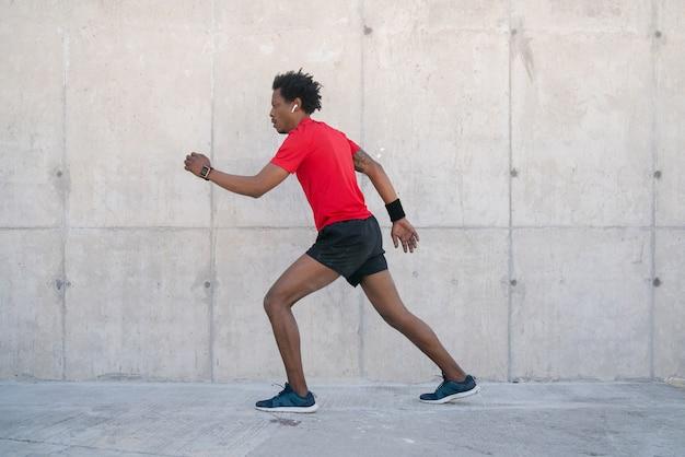 路上で屋外で走ったり運動したりするアフロアスレチック男。スポーツと健康的なライフスタイルのコンセプト。