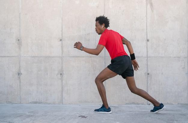 路上で屋外で走ったり運動したりするアフロアスレチック男