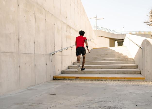 屋外で走ったり運動したりするアフロアスレチック男。スポーツと健康的なライフスタイルのコンセプト。