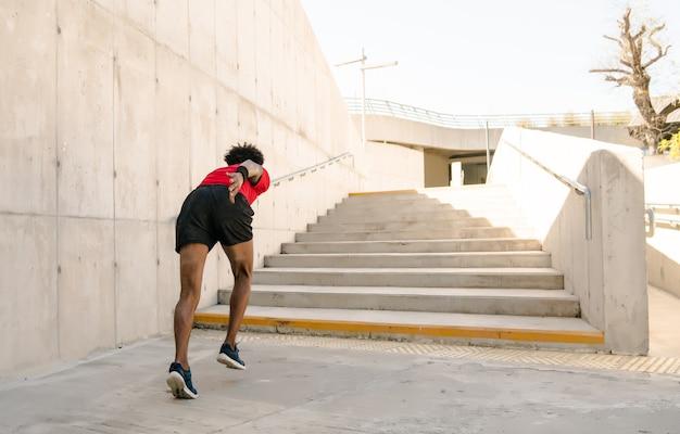 屋外で走ったり運動したりするアフロアスレチック男