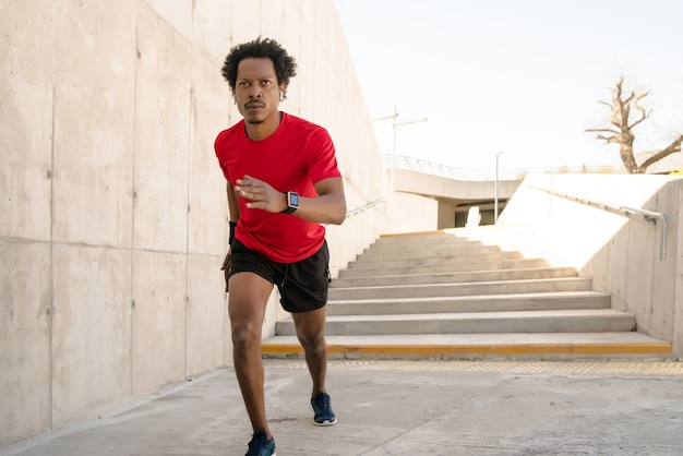 Afro athletic man running and doing exercise outdoors on the street. sport and healthy lifestyle concept.