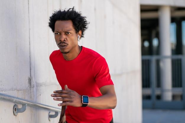 Uomo atletico afro che corre e fa esercizio all'aperto sulla strada