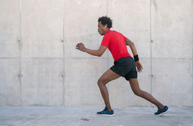 Afro athletic man running and doing exercise outdoors on the street