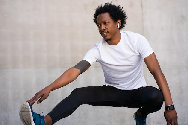 屋外で運動する前に、足を伸ばしてウォーミングアップするアフロアスリートの男性。スポーツと健康的なライフスタイルのコンセプト。
