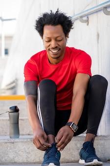 靴ひもを結び、屋外での運動の準備をしているアフロアスリートの男性。スポーツと健康的なライフスタイルのコンセプト。