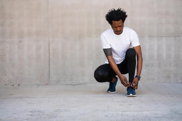 Uomo atletico afro che lega i lacci delle scarpe e si prepara per allenarsi all'aperto. sport e concetto di stile di vita sano.