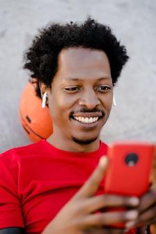 携帯電話を使用し、屋外で運動した後にリラックスするアフロアスリートの男性。スポーツとテクノロジーのコンセプト。