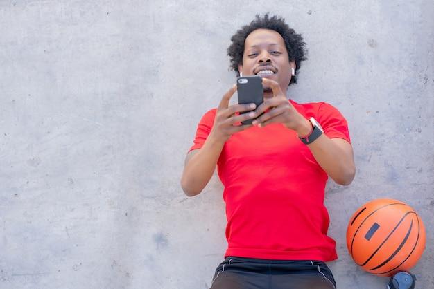 携帯電話を使用し、屋外で運動した後にリラックスするアフロアスリートの男性。