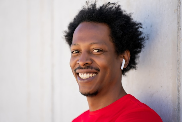 Afro athletic man wearing ear pods and smiling against the wall