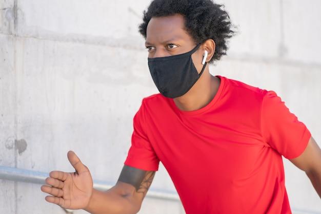 フェイスマスクを着用し、屋外で走っているアフロアスレチック男。新しい通常のライフスタイル。スポーツと健康的なライフスタイルのコンセプト。