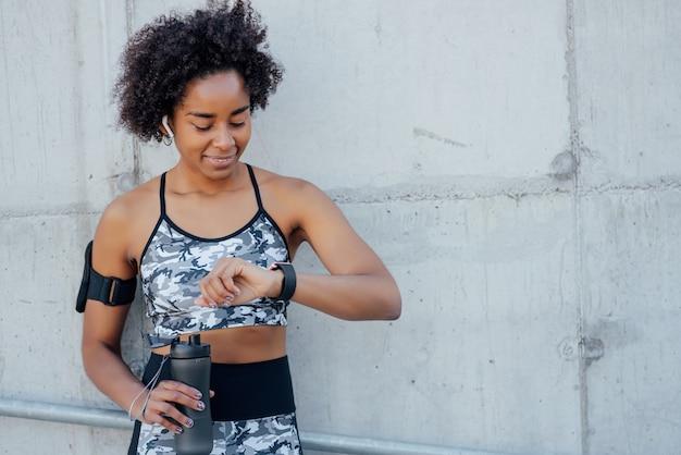 屋外で運動しながらスマートウォッチで時間をチェックするアフロアスリートの女性。スポーツと健康的なライフスタイルのコンセプト。