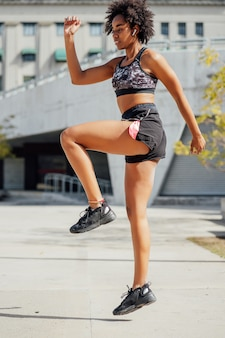 Afro athletic woman doing exercise outdoors on the street. sport and healthy lifestyle concept.