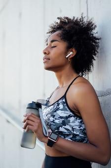 水を飲み、屋外で運動した後にリラックスするアフロアスリート女性。スポーツと健康的なライフスタイルのコンセプト。