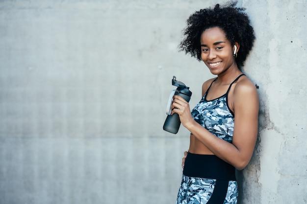 水を飲み、屋外で運動した後にリラックスするアフロアスリート女性。スポーツと健康的なライフスタイル。